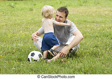 father playing football with his son - The father or man...