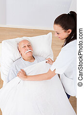 Doctor Covering Senior Man With Blanket