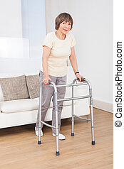 Senior Woman Using Walking Frame - Full length portrait of...