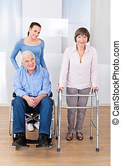 Disabled Senior Couple With Caregiver - Portrait of disabled...
