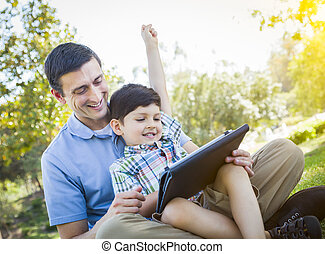 Handsome Mixed Race Father and Son Playing on Computer Tablet
