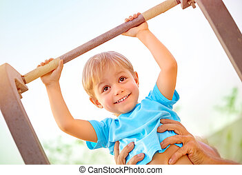 Happy child lifting on crossbar - Closeup portrait of little...