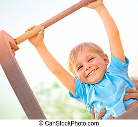 Little boy catch up on the horizontal bar - Little boy with...
