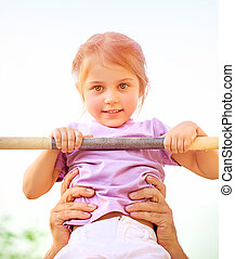 Little girl on crossbar - Portrait of cute little girl...
