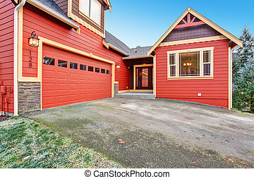 House exterior. Red clapboard siding house with stone wall...