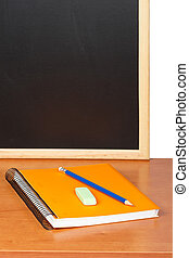 Education - A notebooks and pencil against black chalkboard....
