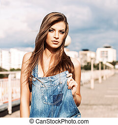 beautiful girl with long silky hair in denim short overalls...