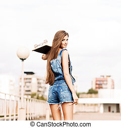 beautiful lady with long silky hair in denim short overalls...