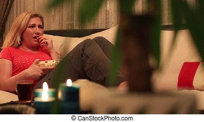 blonde women watching tv 2 - dolly shot blonde women eating...