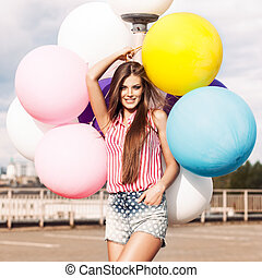 young beautiful lady holding bunch of bright balloons -...