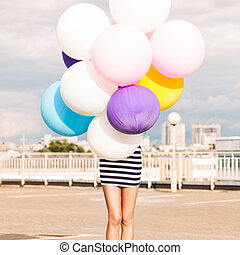 girl in black and white striped short dress and white high top sneakers hides in bunch of multicolored balloons