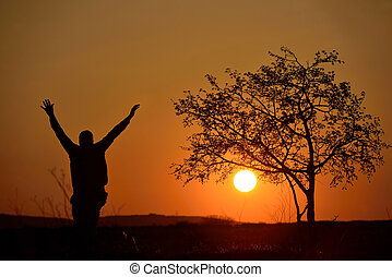 Silhouette of a tree and a man in sunset background - people...