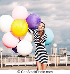 girl in black and white striped short dress and white high top sneakers sends air kiss holding bunch of multicolored balloons