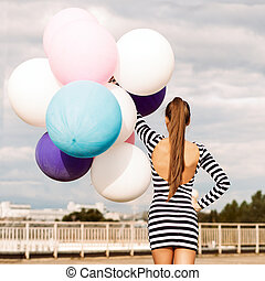 back view of girl in open-back black and white striped short dress and white high top sneakers holds a bunch of multicolored balloons