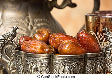 Dates at Ramadan time - Silver bowl filled with dates as...