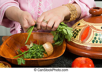Islamic tajine cooking - Hands of a woman adding vegetables...