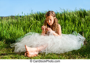 Young girl sitting in green meadow.