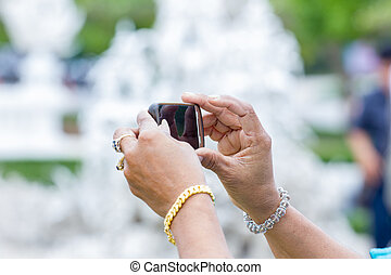 rich woman hands taking a picture at a temple in Thailand