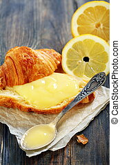 Lemon curd and teaspoon on a slice of fresh croissant.