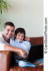 Father and son playing with a computer