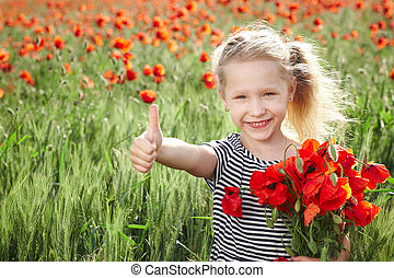 Happy little girl on poppy meadow giving thumb up - Happy...