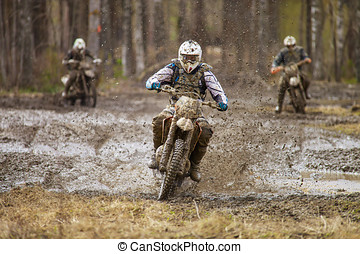 Motocross Race - Motocross driver on wet and muddy terrain...