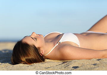 Beautiful woman sunbathing lying on the beach with the sky...