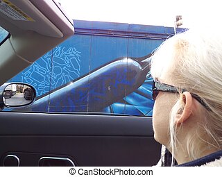 Woman looking out of a convertible on a Graffitti