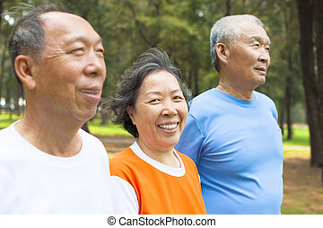 happy senior woman looking at camera with her brothers