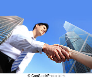 business people shaking hands with city background focus on...