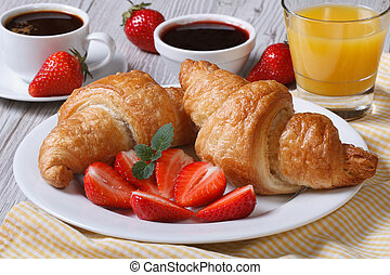 breakfast: croissants with strawberries and coffee, juice