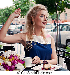 a beautiful young blond girl with a toothy smile in summer dress at the table in pavement cafe is waving someone