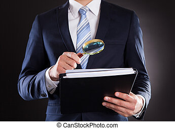 Businessman Examining Documents With Magnifying Glass -...