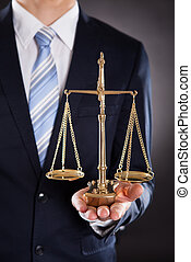 Businessman Holding Justice Scale - Midsection of...