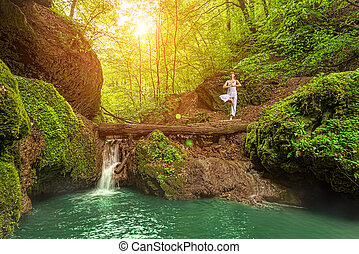 Relaxation, Woman practices yoga at the waterfall - Still,...