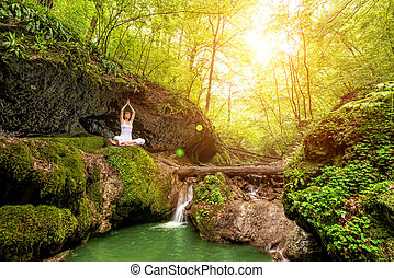 Woman practices yoga at the waterfall. Sukhasana pose