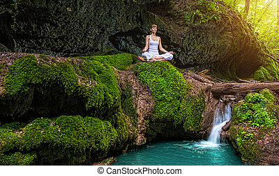 Woman practices yoga in nature, the waterfall sukhasana pose...