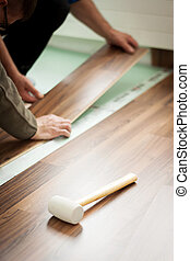 hands laying laminate
