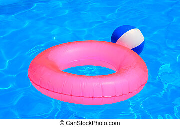 Colorful inflatable ball and round tube floating in swimming...