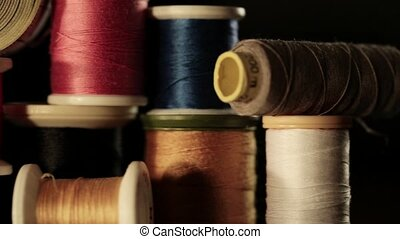 Reels of thread. - Close up pan of bobbin in different...