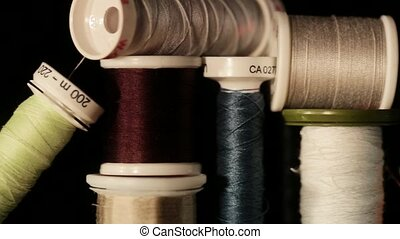 Reels of thread - Close up pan of bobbin in different colors...
