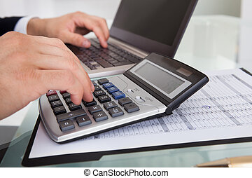 Businessman Calculating Expense In Office - Cropped image of...