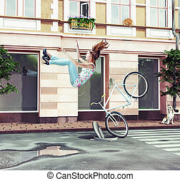 girl falling off her bicycle on city street creative concept...