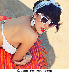 a beautiful young girl in retro look with red lips in a...