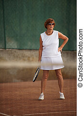 Senior woman plays tennis - Active senior woman in her 60s...