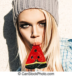 Portrait of sexy blond girl with smokey eye makeup who sucks watermelon lollipop with her plump passionate lips
