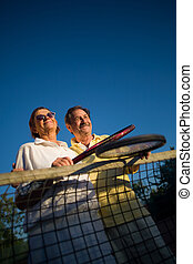 Senior tennis players - Active senior couple is posing on...