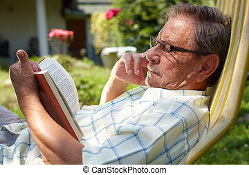 Senior man reading outdoor - Healthy looking senior man is...