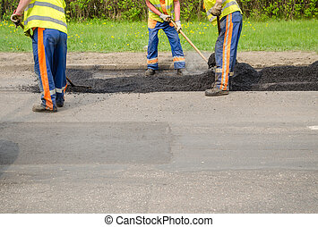 teamworker smoothing asphalt pavement new road - teamworker...