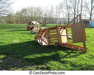 Playground - Wind damaged childrens playhouse and swingset...